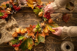Making wreath autumn colorful leaves and natural materials on rustic wooden boards. Top view women's hands make round wreath autumn harvest and foliage on brown wooden table. Decoration for interior.