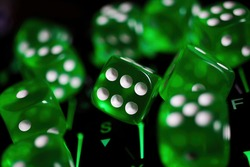Makro closeup of group isolated green  dice cubes with face number 6 in center on illuminated computer keyboard - decision making tool concept (focus on central point upper row of dice 6 in center)