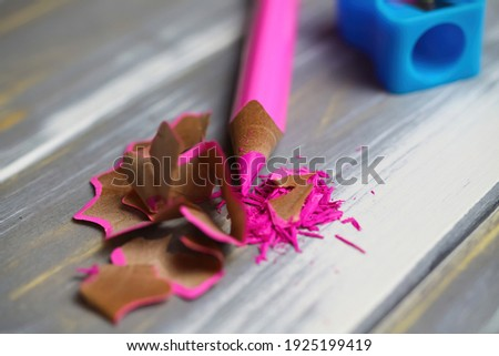 Makro closeup of isolated pink sharp crayon pencil with curly wood chips shavings on table with blue plastic sharpener background (focus on tip of pencil) Stock foto ©