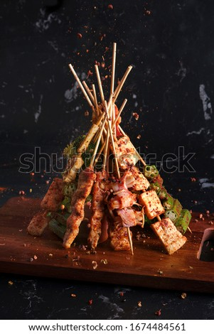 Mala grilled barbecue (BBQ) with Sichuan pepper, with falling seasonings mala powder and chilli,Hot and spicy and delicious street food on black background. Stock photo ©