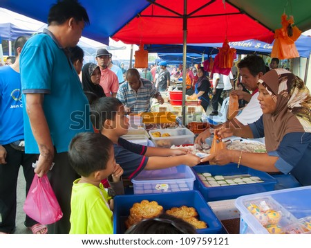 MALACCA, MALAYSIA-AUG 06: Unidentified traditional dish seller attends to a customer at Pasar Ramadan Merlimau on August 06, 2012 in Malacca, Malaysia. Muslims around the world start fasting today.