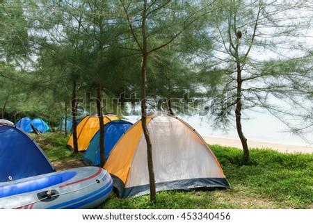 MALACCA, MALAYSIA - February 8 2016 : Camping tents and boat near the beach at Pangkalan Balak Beach Melaka, Malaysia #453340456