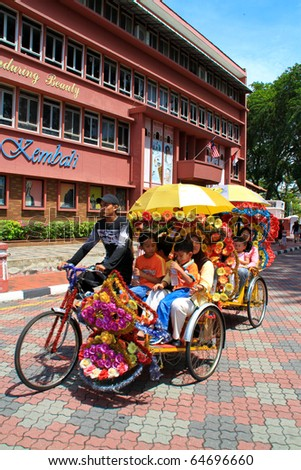MALACCA, MALAYSIA - NOVEMBER 6: Tourist on the famous hi-tech decorative trishaw on November 6, 2010 in Malacca. The trishaw ride is a major attraction for visitors to see the city of Malacca.