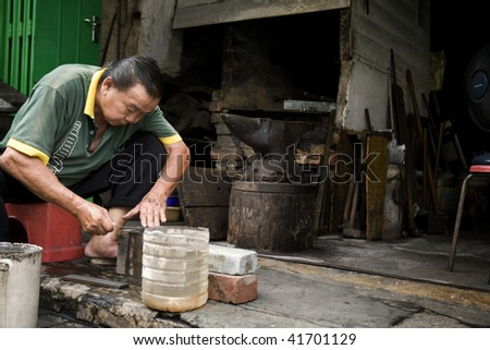 MALACCA - OCTOBER 31: A blacksmith sharpens a knife he had just made, he is one of the very few living traditional blacksmith here in the historic city of Malacca.  October 31, 2009 in Malaysia.