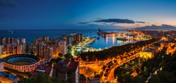 Malaga, Spain. Aerial view of City Hall? port and Bullring arena with illuminated buildings and Mediterranean sea in Malaga, Andalusia, Spain at night with sunset sky