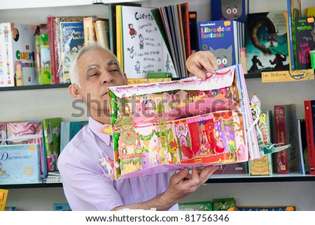 MALAGA, SPAIN - JUNE 11: Unidentified seller shows a children book during the 2011 Malaga Book Fair on June 11, 2011 in Malaga, Spain