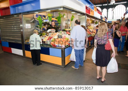 MALAGA, SPAIN - JUNE 10: Unidentified sellers pack fruits at their shop in the popular central market on June 10, 2011 in Malaga, Spain.  It was renovated in 2010 and it was reopened on March 2011.