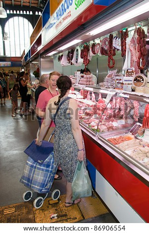 MALAGA, SPAIN - JUNE 10: Unidentified sellers pack meat at their shop in the popular central market on June 10, 2011 in Malaga, Spain. It was renovated in 2010 and it was reopened on March 2011.