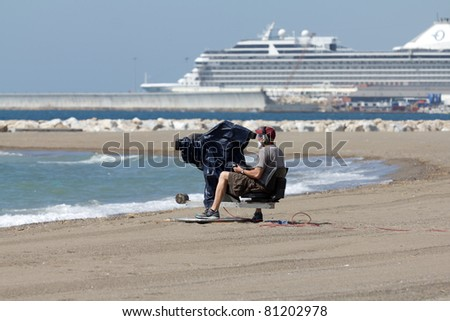 MALAGA, SPAIN - MAY 28: An unidentified cameraman broadcasts an air show at Malagueta Beach at Spanish Armed Forces Day on May 28, 2011 in Malaga, Spain.