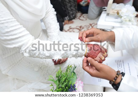 Malay Couple Wearing A Wedding Ring. Selective Focus And Shallow DOF. The most important part of the Malay wedding solemnization, which can be done in a mosque or even in the bride home.