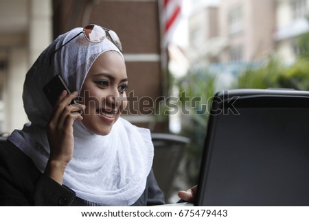 Malay woman using cell phone.