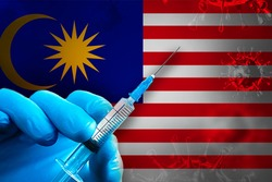 Malaysia Covid-19 Vaccination Campaign. A hand in a blue rubber glove holds a syringe with covid-19 virus vaccine in front of Malaysia flag. Coronavirus vaccination concept