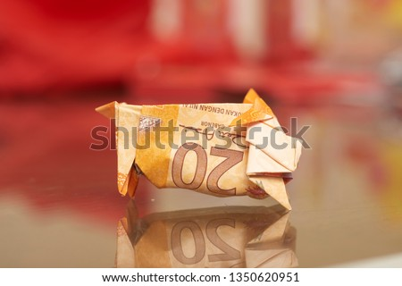 Malaysia Currency (MYR): Piggy bank origami made using MYR and a coin with blurry background. Concept shows saving, investment and banking. #1350620951