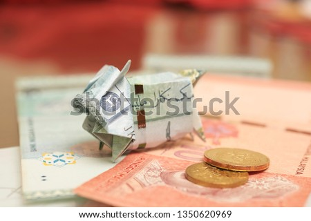Malaysia Currency (MYR): Piggy bank origami made using MYR and a coin with blurry background. Concept shows saving, investment and banking. #1350620969
