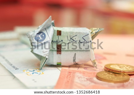 Malaysia Currency (MYR): Piggy bank origami made using MYR and a coin with blurry background. Concept shows saving, investment and banking. #1352686418
