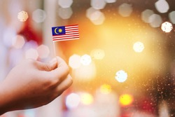 Malaysia Independence Day celebration.Man's hand holding small Malaysian flag with bokeh background.