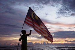 Malaysia Independence Day. Malaysian kids standing with waving Malaysia Flag during sunset moment. Merdeka.