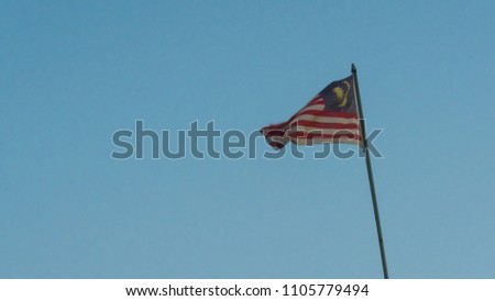 Malaysia national flag sky background at sunrise with golden light on flag #1105779494