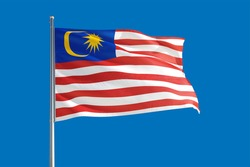 Malaysia national flag waving in the wind on a deep blue sky. High quality fabric. International relations concept.