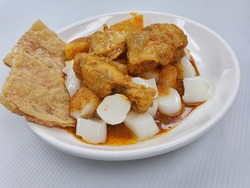 Malaysia Penang local street food, Cantonese traditional steam rice roll dip with soy sauce and curry Chicken with potatoes in white plate, close up isolated in white background.