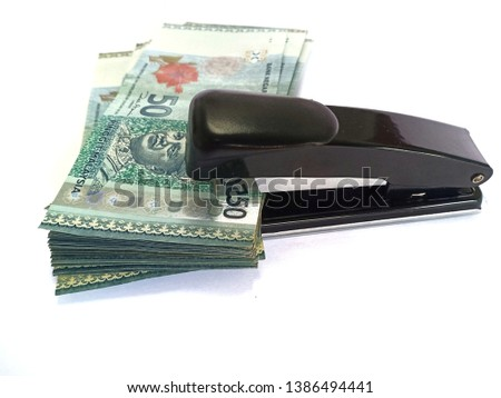Malaysia Ringgit money stapler together .economy effect.  Malaysian finance . with hand pushing stapler . isolated on white background stock photo -image