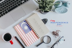 Malaysia's Independence day concept.Laptop,Coffee,Green plant and a notebook with malaysian flag and text Happy Independence Day 31st August also known as Hari Merdeka