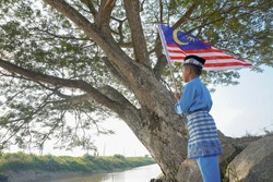 Malaysian boy in Malay traditional suit waving Malaysia flag. Malaysia Independence Day.