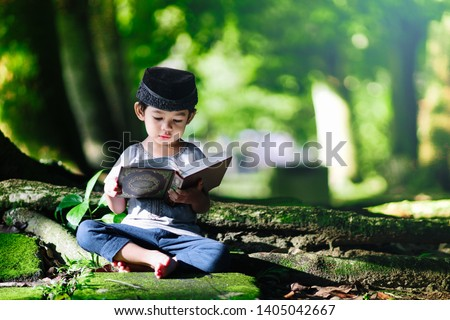 Malaysian muslim boy reciting al Quran at beautiful green nature background with a copy space in Ramadan fasting month