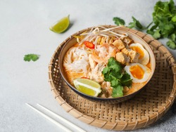 Malaysian noodles laksa soup with chicken, prawn and tofu  in a bowl on grey background
