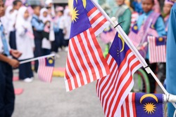 Malaysian primary students with Malaysian Flag during the celebration of Hari Kemerdekaan, the Independence Day of Malaysia.