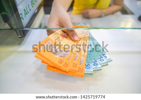 Malaysian Ringgit , A women giving some Malaysian Ringgit, Malaysia currency, money exchange for MYR domination note.