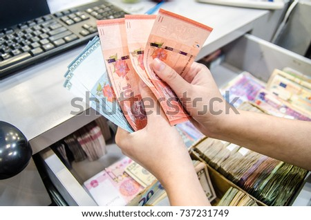 Malaysian ringgit (MYR), Malaysia money, Women counting money currency of Malaysia. Exchange money for Malaysian ringgit (MYR), business and finance concept.