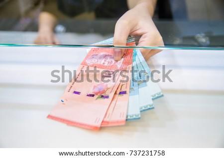 Malaysian ringgit (MYR), Malaysia money, Women giving money currency of Malaysia. Exchange money for Malaysian ringgit (MYR), business and finance concept.