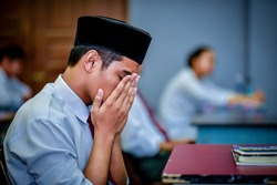 Malaysian students pray before answering the final exam.
