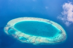 Maldive Islands in the turquoise ocean and white clouds, top view from the height of the plane