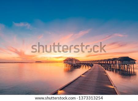 Maldives island sunset. Water bungalows resort at islands beach. Indian Ocean, Maldives. Beautiful sunset landscape, luxury resort and colorful sky. Artistic beach sunset under wonderful sky