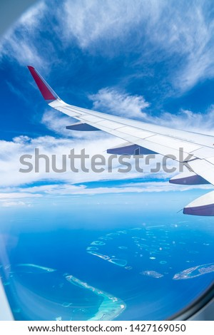 Maldives islands top view from airplane window with airplane's wing #1427169050