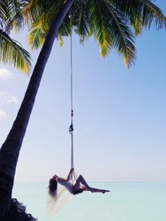 Maldives woman swinging near the Indian ocean. Young beautiful woman relaxing in swing hanging on coconut palm at tropical beach. Sexy amazing young girl swinging on Maldivian beach. Luxury vacation.