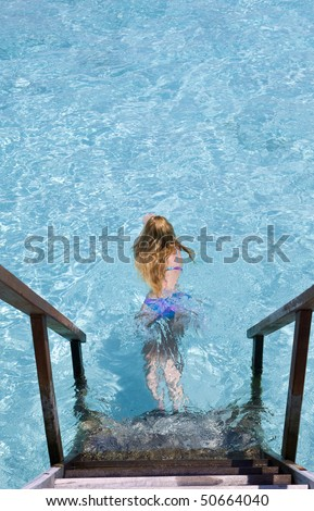Maldives.  Young sports woman swims from steps of villa on water.
