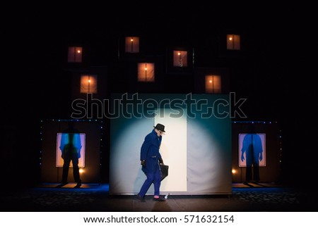 Male actor in a blue suit plays a role in the background of a theater stage with scenery for the play. #571632154
