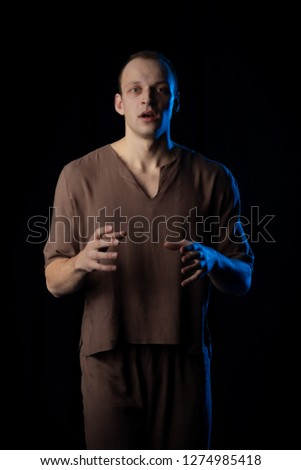 Male Actor on stage plays emotions in blue theatrical light #1274985418