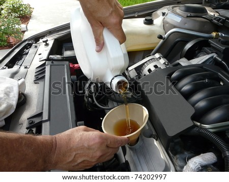 Male adding oil with a funnel after a do-it-yourself oil change.