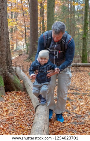 Male adult and female toddler out for a hike at the forrest playground in the Bavarian Forrest National Park balance walking some round wood side barriers