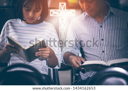 Male adults are reading the Bible holy bible by pointing to the character and to share the gospel to youth. The cross symbol, glow over the books of the Bible, Concepts of Christianity. #1434162653