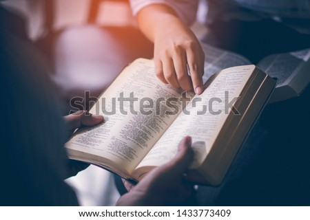 Male adults are reading the Holy bible by pointing to the character and to share the gospel to youth. The cross symbol, The books of the Bible, Concepts of Christianity. #1433773409