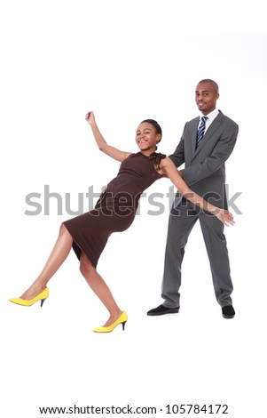 Male African American business manager in suit and tie, catching a female colleague wearing a brown dress and yellow shoes, in a trust exercise for bonding and team work in office