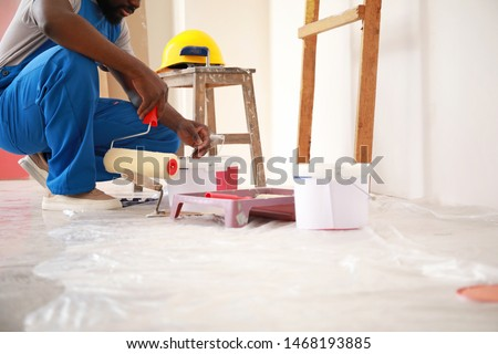 Male African-American decorator doing repair in room Stock photo ©