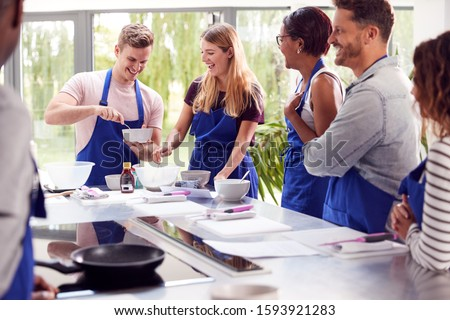 Male And Female Adult Students Measuring Ingredients In Cookery Class In Kitchen Stock photo ©