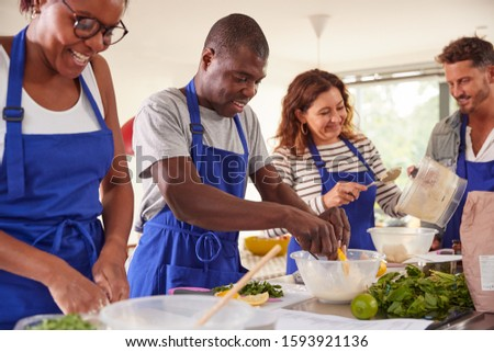 Male And Female Adult Students Preparing Ingredients For Dish In Kitchen Cookery Class Stock photo ©