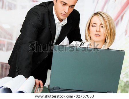 Male and female architects behind laptop and blueprints, looking serious